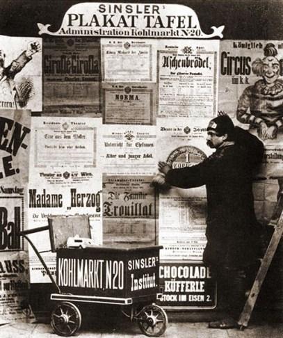 Plakatierer an Plakattafel mit Leiterwagen