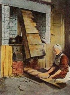 Bäckerin schiebt Brote in den Backofen