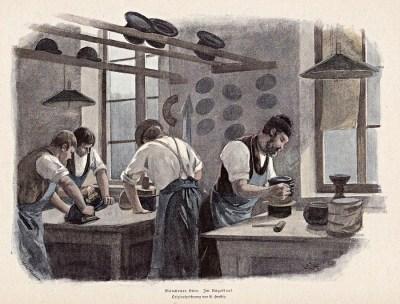 Vier Hutmacher arbeiten in der Werkstatt und streichen Hüte glatt