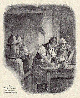 zwei Hutmacher stülpen den Filz über Hutformen