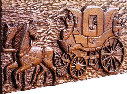 holzgeschnitztes Wandrelief: zwei Pferde ziehen Postkutsche; Postkutscher mit Posthorn