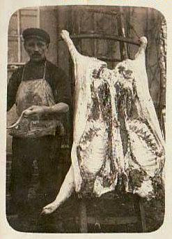 altes Foto: Metzger steht neben aufgeschnittenem und aufgehangenem Schwein