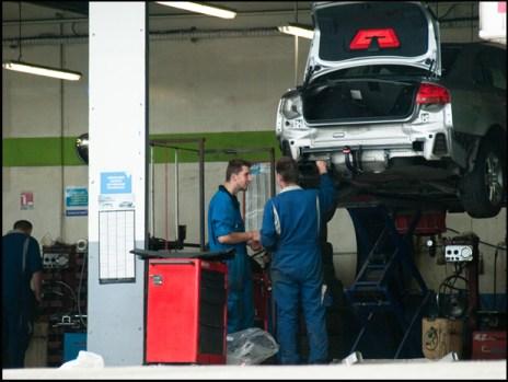 Foto: Automechaniker steheh neben Auto, welches sich auf einer Hebebühne befindet.