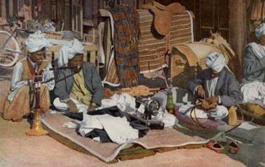 indischer Schneider sitzt auf Teppich mit Nähmaschine und schneidert