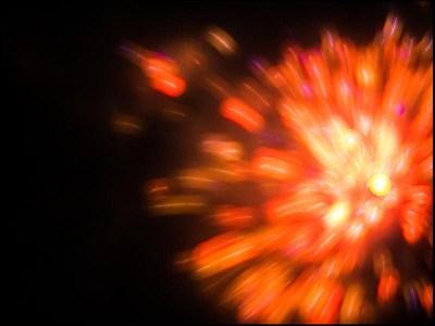 Foto: rötliche Farbexplosion von einem Feuerwerk