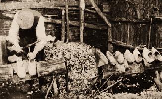 altes sw-Foto: Mann beim Aushöhlen von Holzpantinen