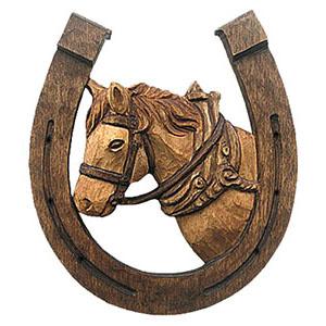 holzgeschnitzes Handwerkszeichen: nach oben offenes Hufeisen, durch das ein Pferdekopf schaut