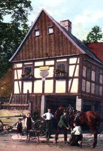 farbige PK: Hufschmied bei der Arbeit vor einem bayrischen Fachwerkhaus