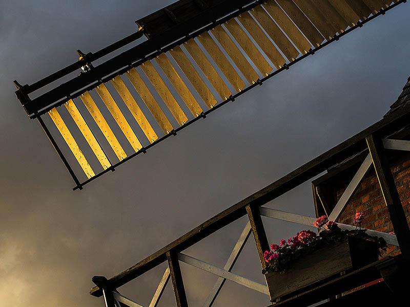 Foto: in goldenes Licht getauchter Windmühlenflügel
