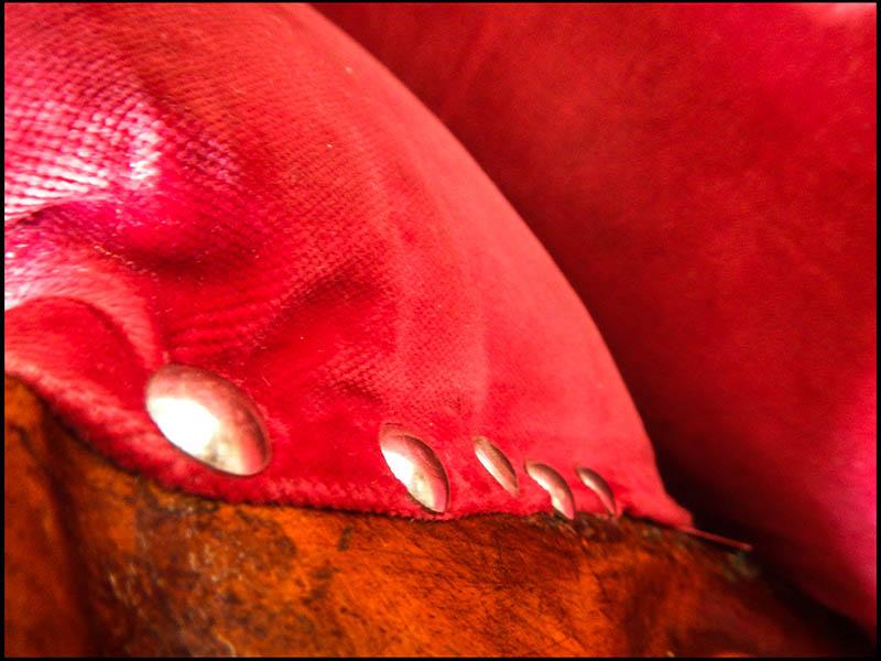 Farbfoto: Nahaufnahme: rotes Polster, Polsternägel