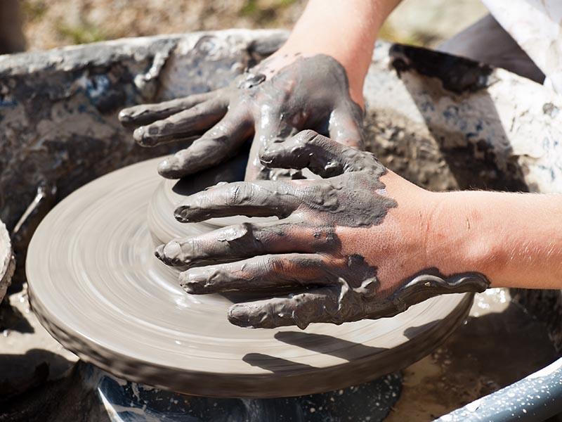 Foto: Hände formen Gefäß an Töpferscheibe