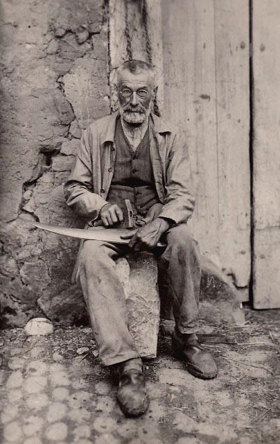 altes sw-Foto: alter Mann mit Nickelbrille sitzt auf einem Stein und beschlägt Blech mit einem Hammer