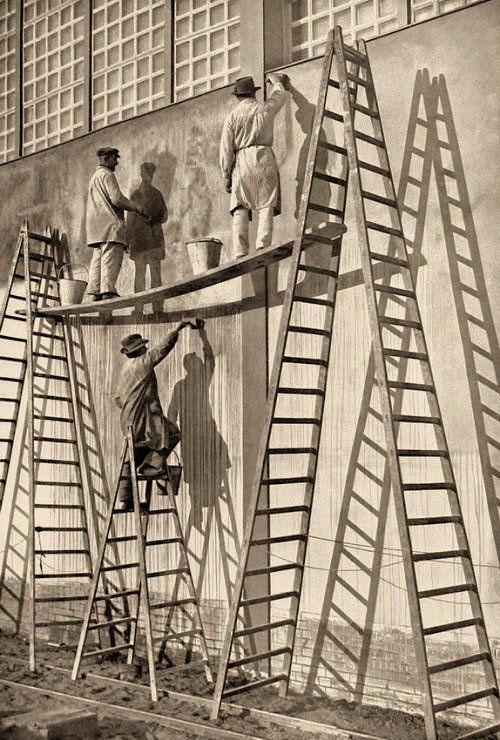 s/w Foto: drei Fassadenmaler auf bis zu 5m hohen Bockleitern