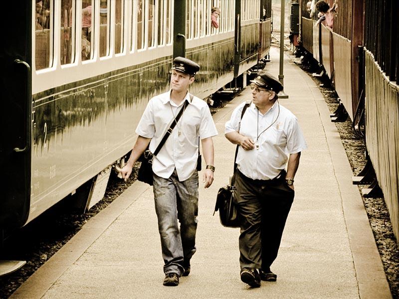 Foto: zwei Schaffner gehen auf einem Bahnsteig zwischen zwei Zügen