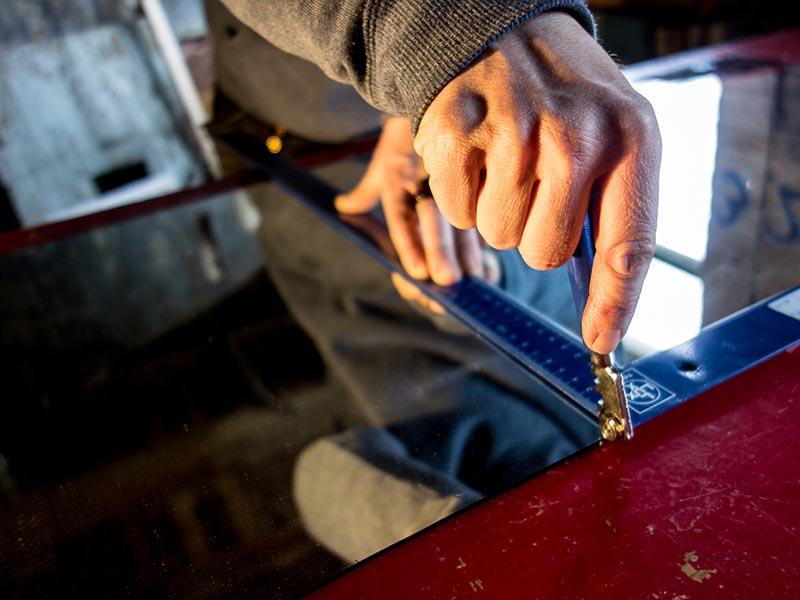 Foto: Nahaufnahme: Spiegel mit Glasschneider schneiden