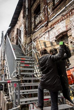 Foto: Frau trägt großen Spiegel die Treppe hinauf