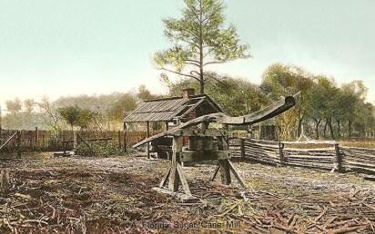koloriertes Foto: eingezäuntes Areal mit verwitterter Holzgestell-Zuckerrohrmühle