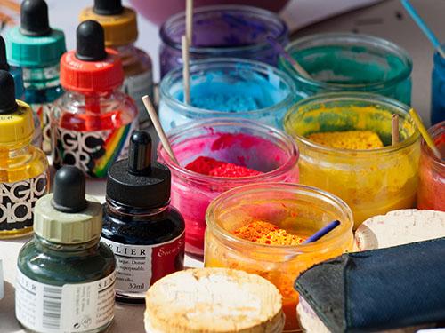 Farbfoto: verschiedene Malfarben in Gläsern und Pipettenflaschen