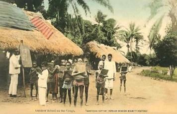 altes koloriertes Foto: im Freien vor Strohhütte Lehrer an einer Stehtafel, rechts daneben mehrere Schüler mit Schreibtafeln im Arm