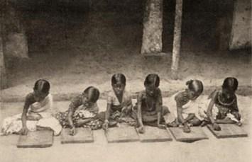 s/w Foto: sechs am Boden sitzende junfe Schüler, die auf Täfelchen schreiben