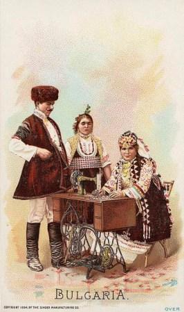 alte Postkarte: eine Frau sitzt an Nähmaschine, Paar steht daneben, alle in Tracht