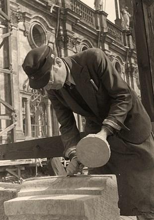 s/w Foto: linkshändiger Steinmetz bearbeitet einen Werkstein mit Meißel und Holzstößel