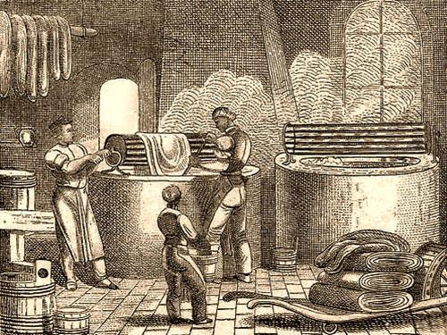 Holzstich: zwei große Färbebecken, ein Färber bewegt Stoff mittels Walze durchs Färbebad während ein anderer in selbigem herrührt, ein Gehilfe hat weitere Stoffballen mit einer Art Schubkarre herbei beschafft und schaut stehend den Färbern zu