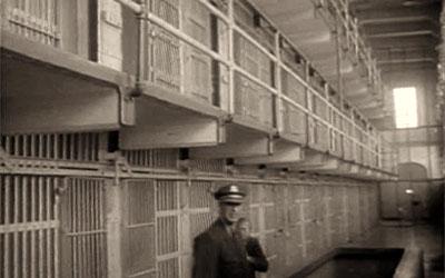 altes s/w Foto: Gefängniswärter im Gang vor Gitter-Zellentüren