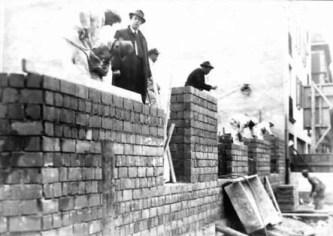 altes s/w-Foto: Maurer beim Hochziehen einer Mauer