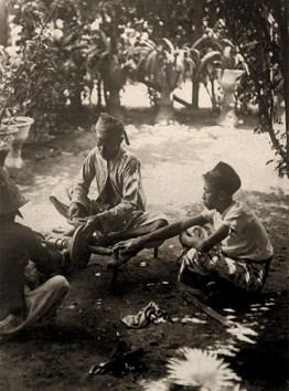 altes sw Foto: drei Messerschleifer mit Schleifvorrichtung am Boden zwischen Blumen im Baumschatten bei der Arbeit