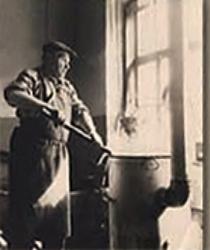 altes sw Foto: Schwarzfärber rührt mit Färbestab im Färbebottich herum