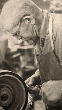 s/w Foto: Messerschmied schleift Messer am Schleifstein