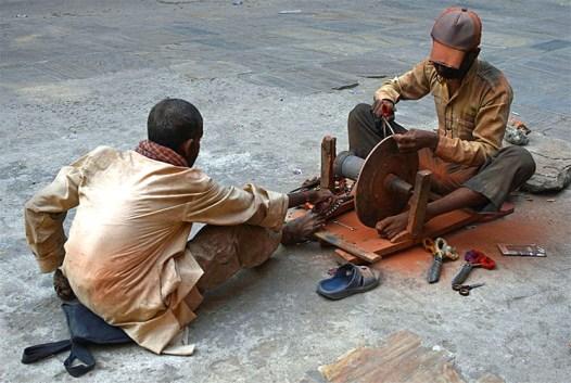 zwei junge nepalesische, mit ihrem Schleifgerät am Boden sitzende, Scherenschleifer- einer bewegt mittels einem Kettenzug die Schleifscheibe und der andere schleift