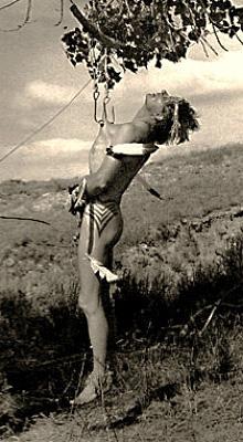 sw Foto: Mann hängt mit seiner Brusthaut an Haken unter einem Baum
