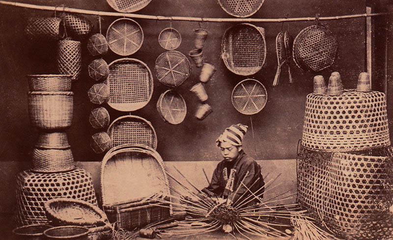 Foto: japanischer Korbmacher sitzt zwischen seinen Körben