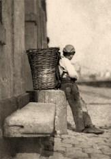 sw Foto: Lumpenjunge ruht sich, mit auf Steinblock abgestelltem Rückenkorb stehend etwas aus