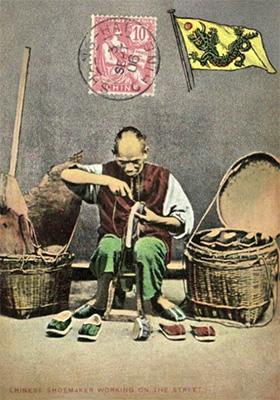 koloriertes Foto: chinesischer Straßenschuster arbeitet auf Hocker sitzend, li Korb mit Leder, re Korb mit fertigen Schuhen
