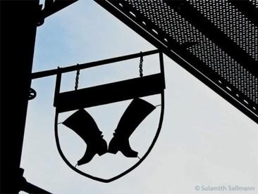 Farbfoto: schmiedeeisernes Wappen mit einem Paar Stiefel