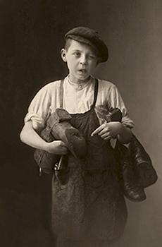 sw Foto: frecher Schusterlehrling mit kaputten Stiefeln unterm Arm - 1910