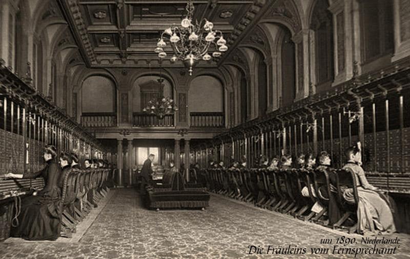 sw Foto: in großem hohen Saal zu beiden Seiten an den Steckpulten sitzende Telefonistinnen