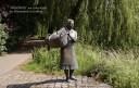 Bronzeskulptur: Frau mit Wäschekorb unterm Arm