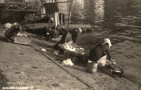 sw Foto: vor Steinpodesten kniende Frauen beim Wäschewaschen