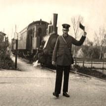 sw Foto: Bahnwart regelt mit Signalflagge Vorfahrt für einen Zug