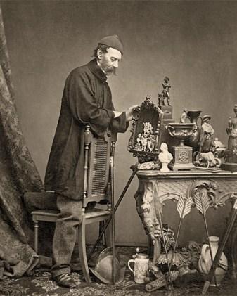 sw Foto: Händler hat vor sich auf einem antiken Tisch und um diesen herum seine Schätze drapiert - 1855