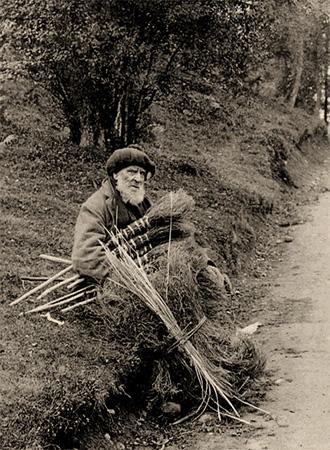 sw Foto: Besenmacher mit Heidekrautbesen und -bündel, der am Wegrand sitzt, um sich auszuruhen