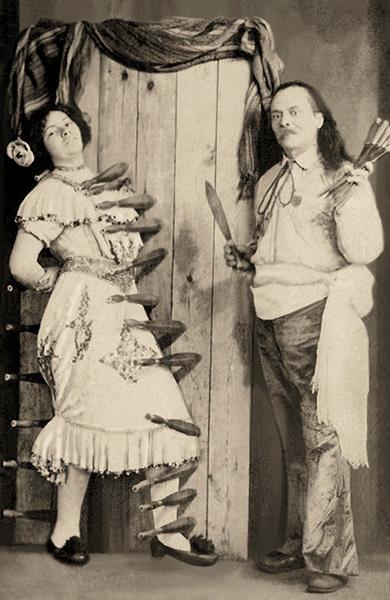 sw PK: Frau vor Zielbrett umrahmt von bereits geworfenen Messern, daneben hält Werfer weitere Messer hoch