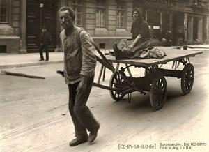 sw Foto: Mann zieht mittels Deichsel und Schultergurt Pritschenwagen, nebst darauf sitzender Frau