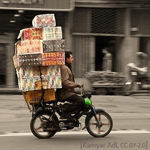 Farbfoto: Lieferant mit großem Paketstapel auf Moped unterwegs