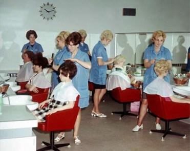 Farbfoto: sechs Friseurinnen in blauen Kittelschürzen bedienen Kundinnen