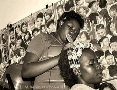 sw Foto: Afrikanische Friseurin dreht Lockenwickler ins Haar einer Kundin - 2016, Tanzania